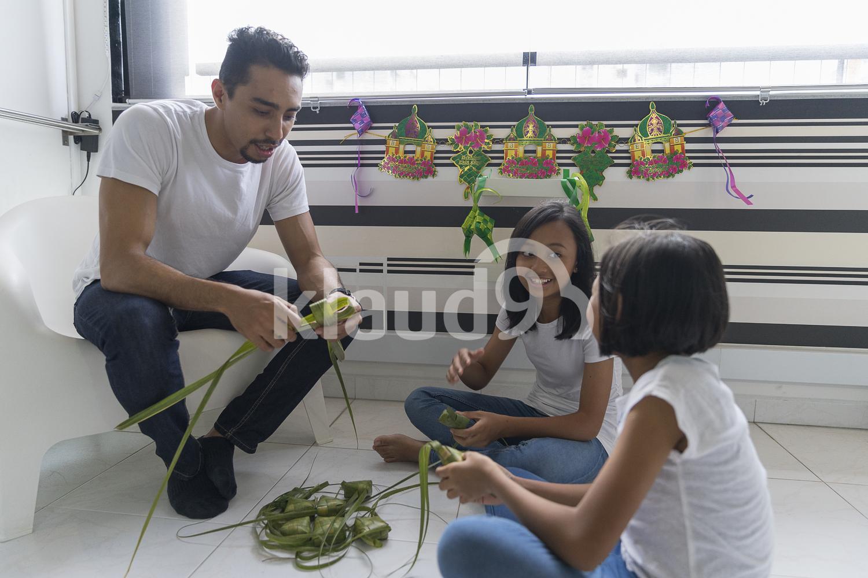 Father teaching his kids how to make ketupat.