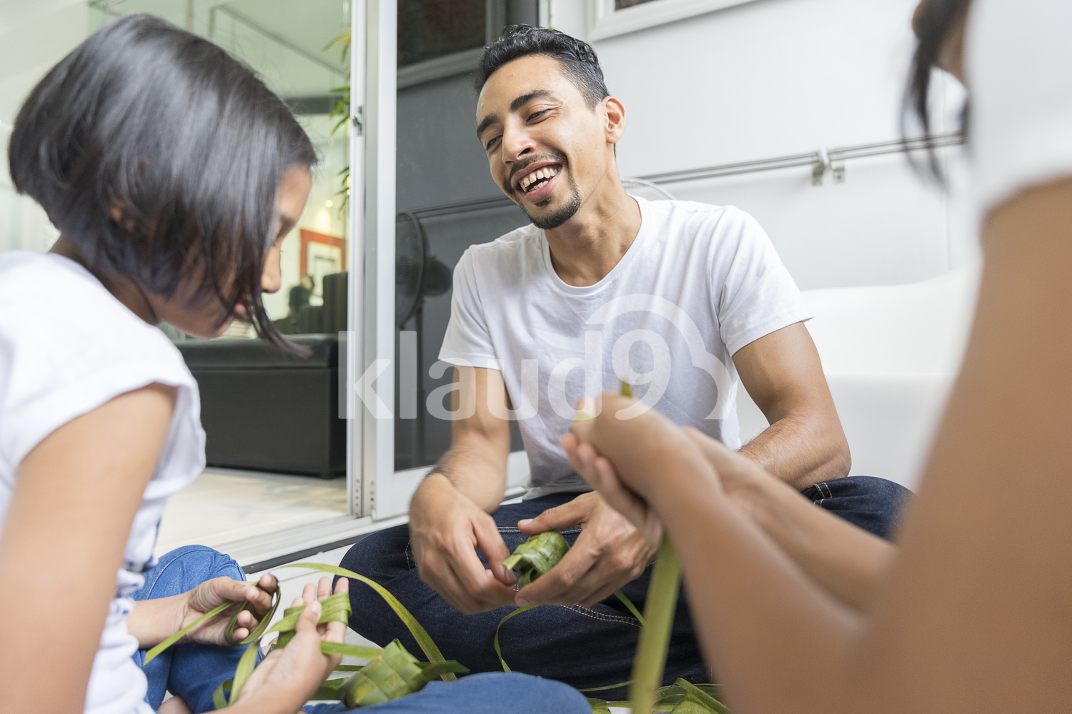 Father teaching his daughters the process of making ketupat