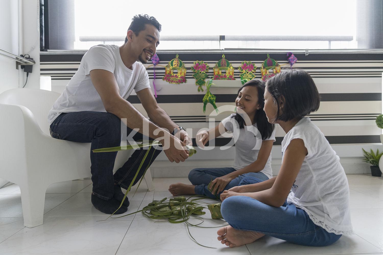 Father teaching his kids how to make ketupat for Hari Raya