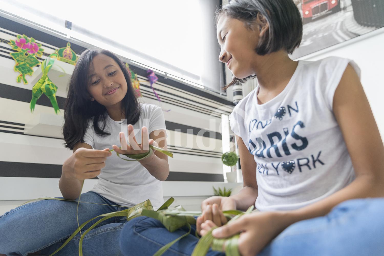 Adorable siblings preparing Ketupats for Hari Raya