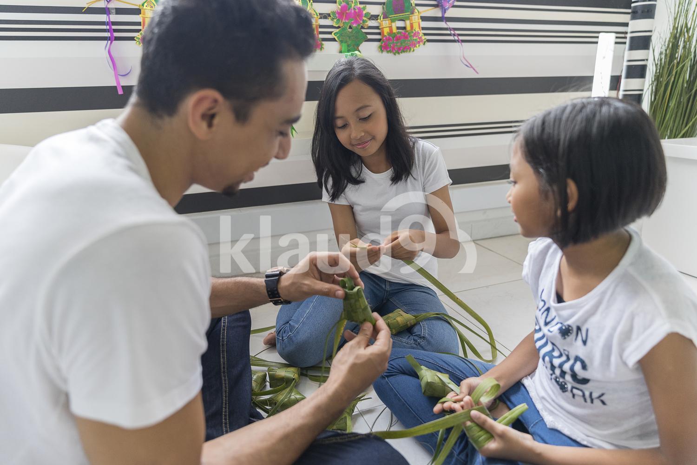 Family making ketupat together during Hari Raya