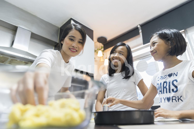 Mother teaching her kids to bake
