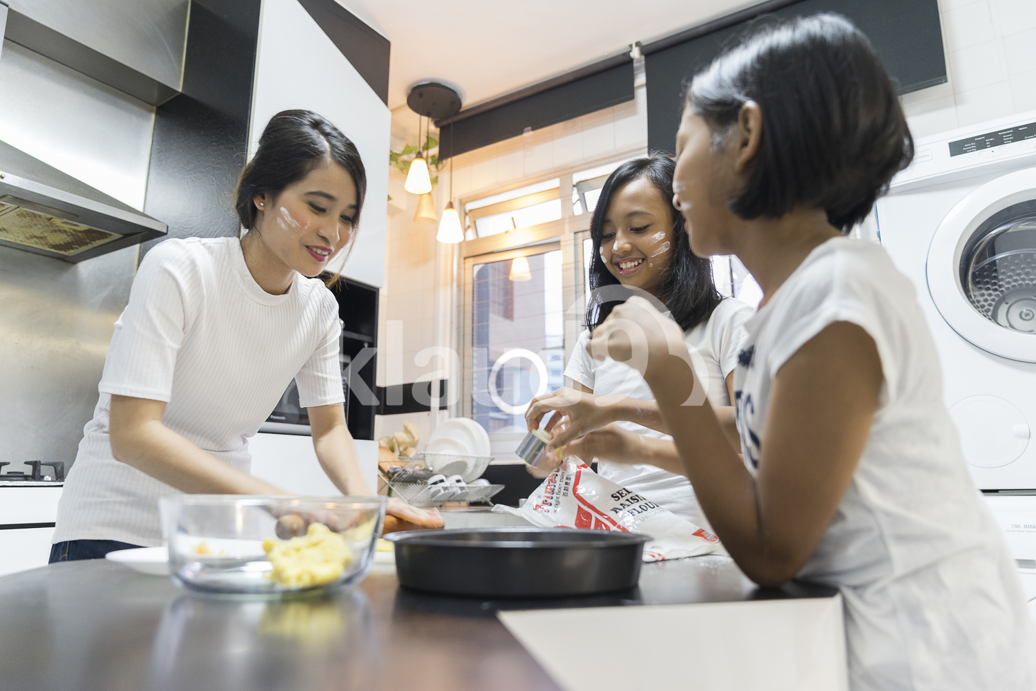 Mother and her daughters having fun during baking