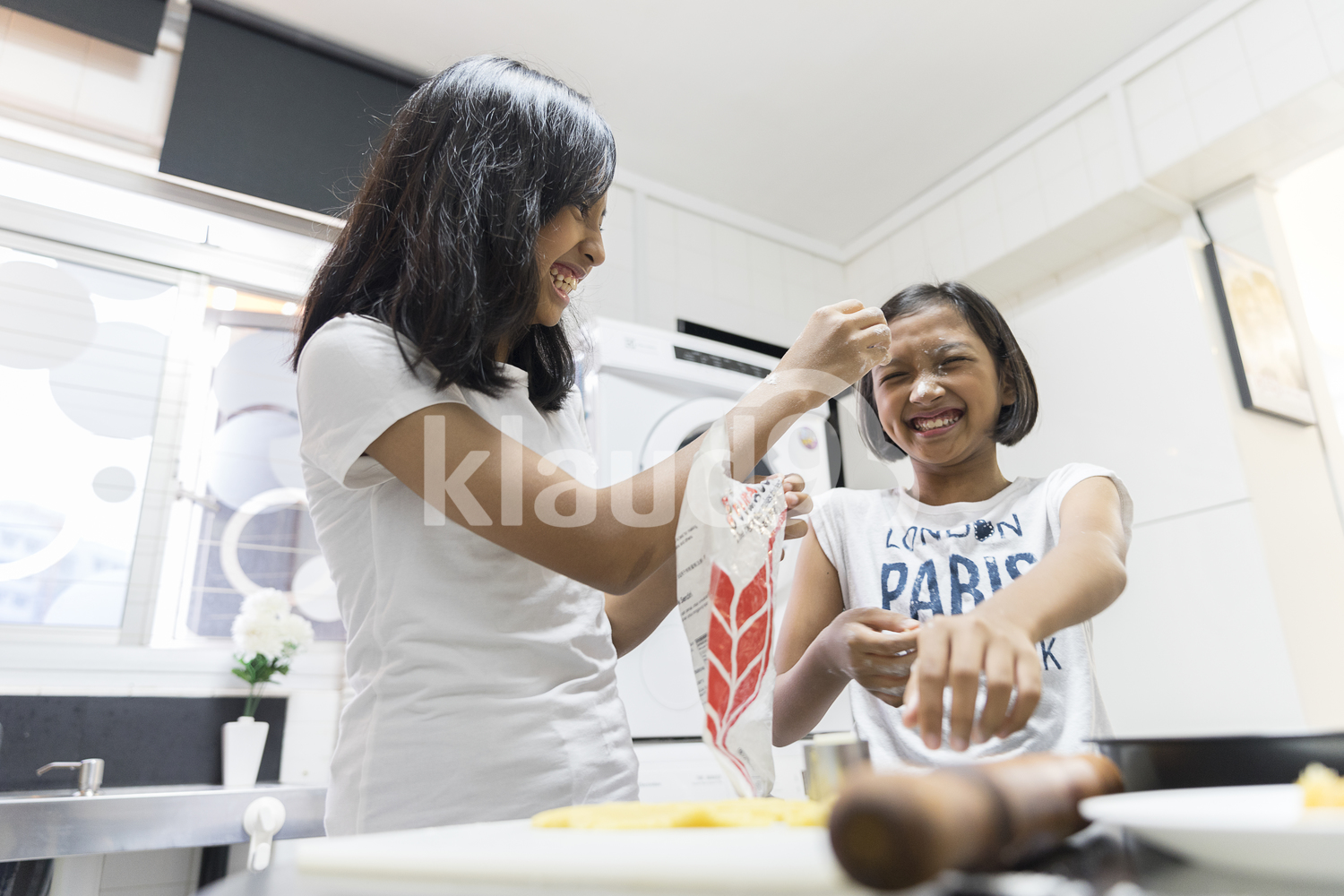 Sisters playing with flour and preparing goodies for Hari Raya