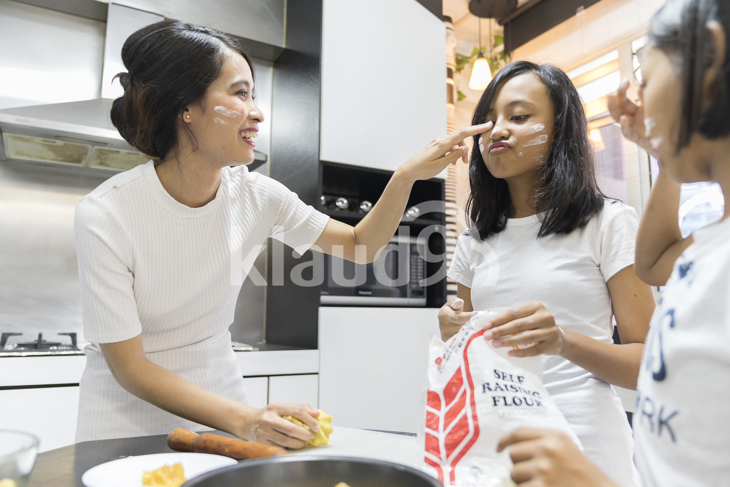 Mother putting flour on her daughter's nose