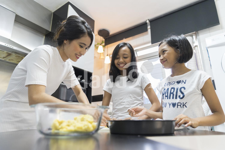 Mother teaching her kids to bake for Hari Raya