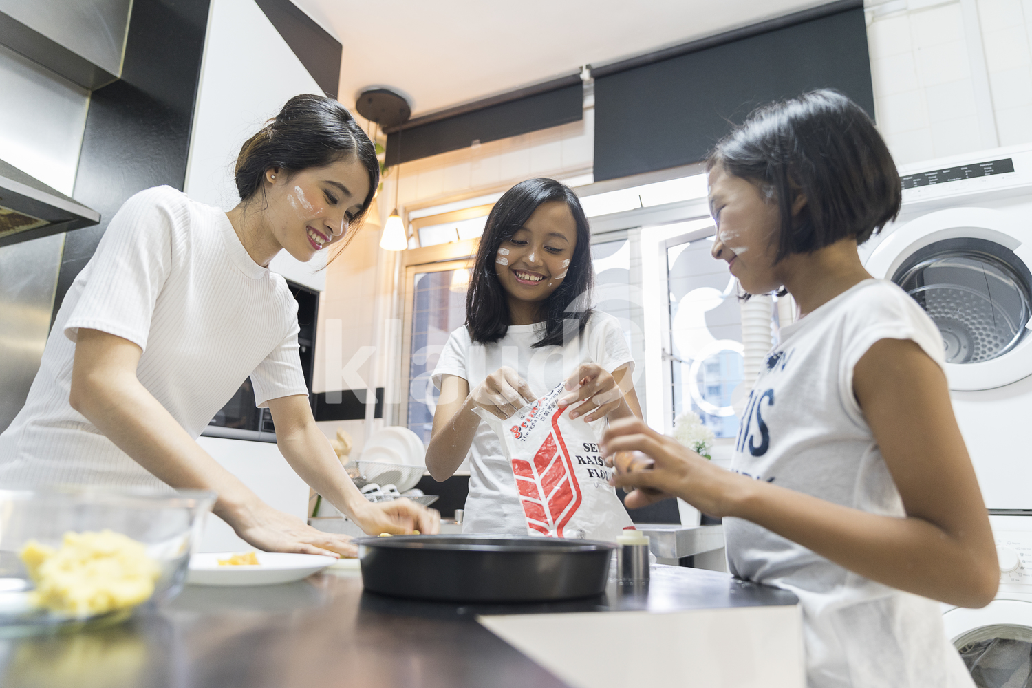 Mother and her daughters having fun during baking for Hari Raya