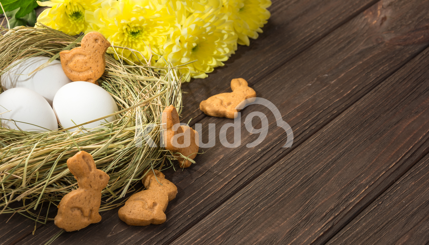 Easter eggs in a straw nest, Easter bunny cookies and yellow flowers