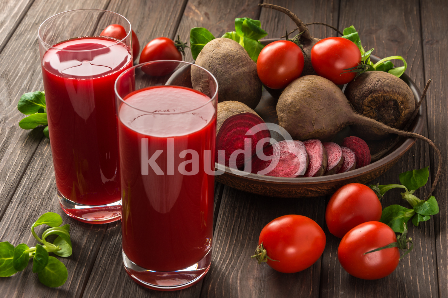 Beet-tomato juice with vegetables on dark wooden background