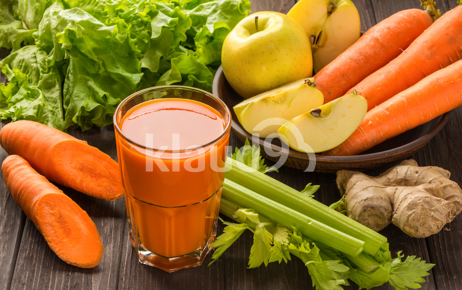 Carrot and apple juice with vegetables on dark wooden background
