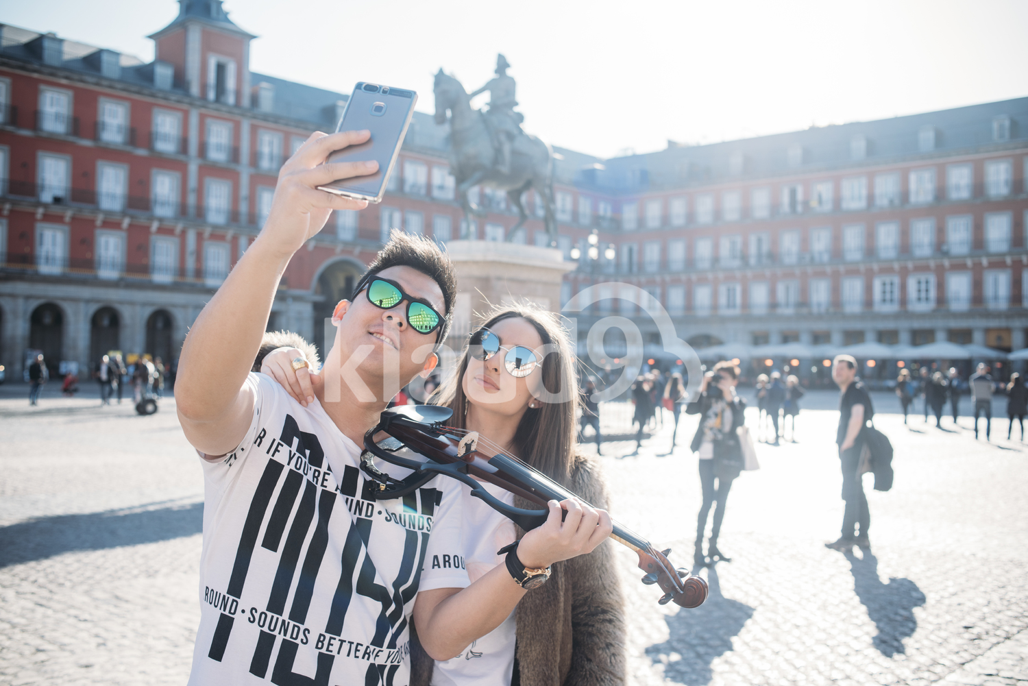 Young violinist taking a selfie with a tourist in Madrid