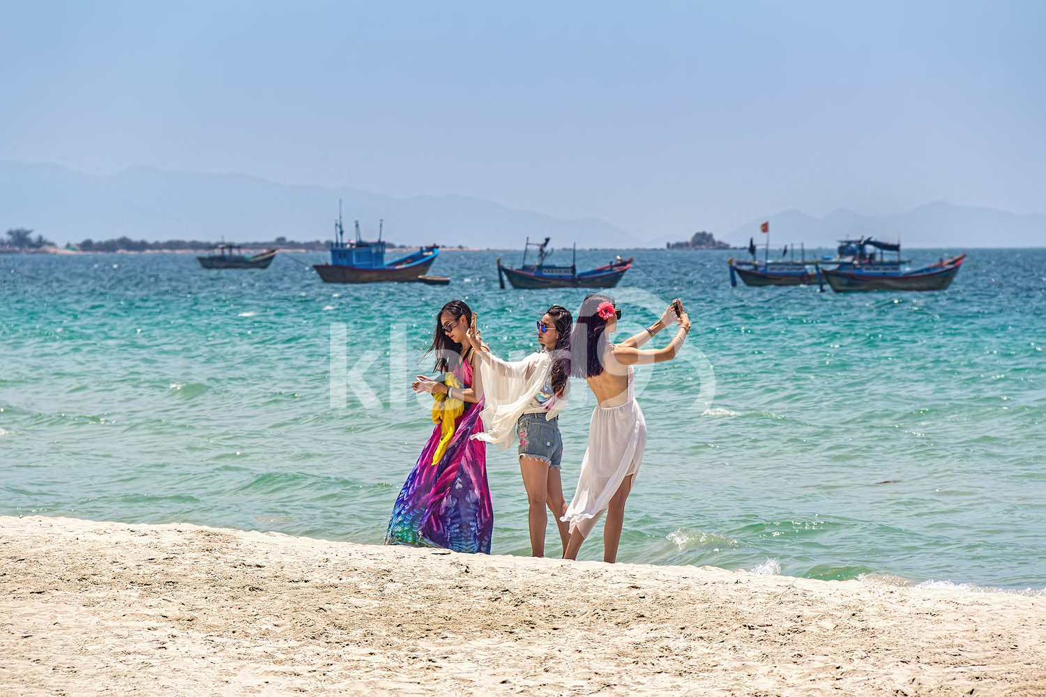 Three young Vietnamese girls taking a selfie on a sandy beach on the South China sea. Vietnam, DocLet Beach Resort