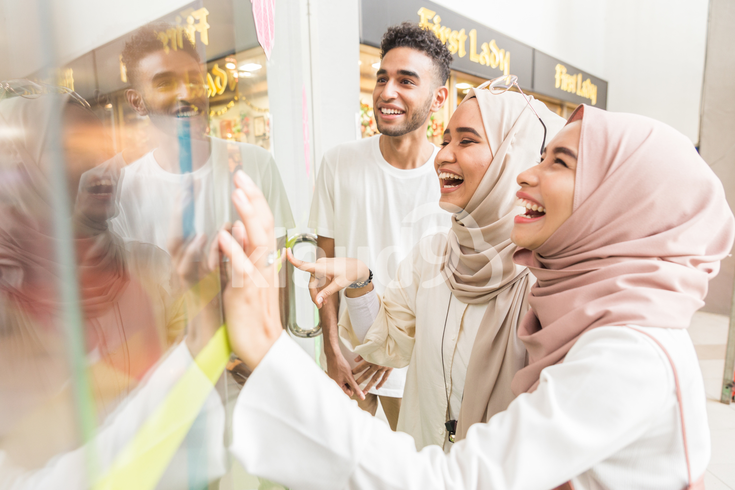 Group of young muslims looking through window
