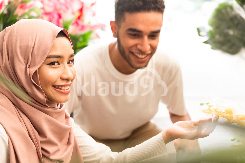 Cute muslim girl admiring flowers and smiling