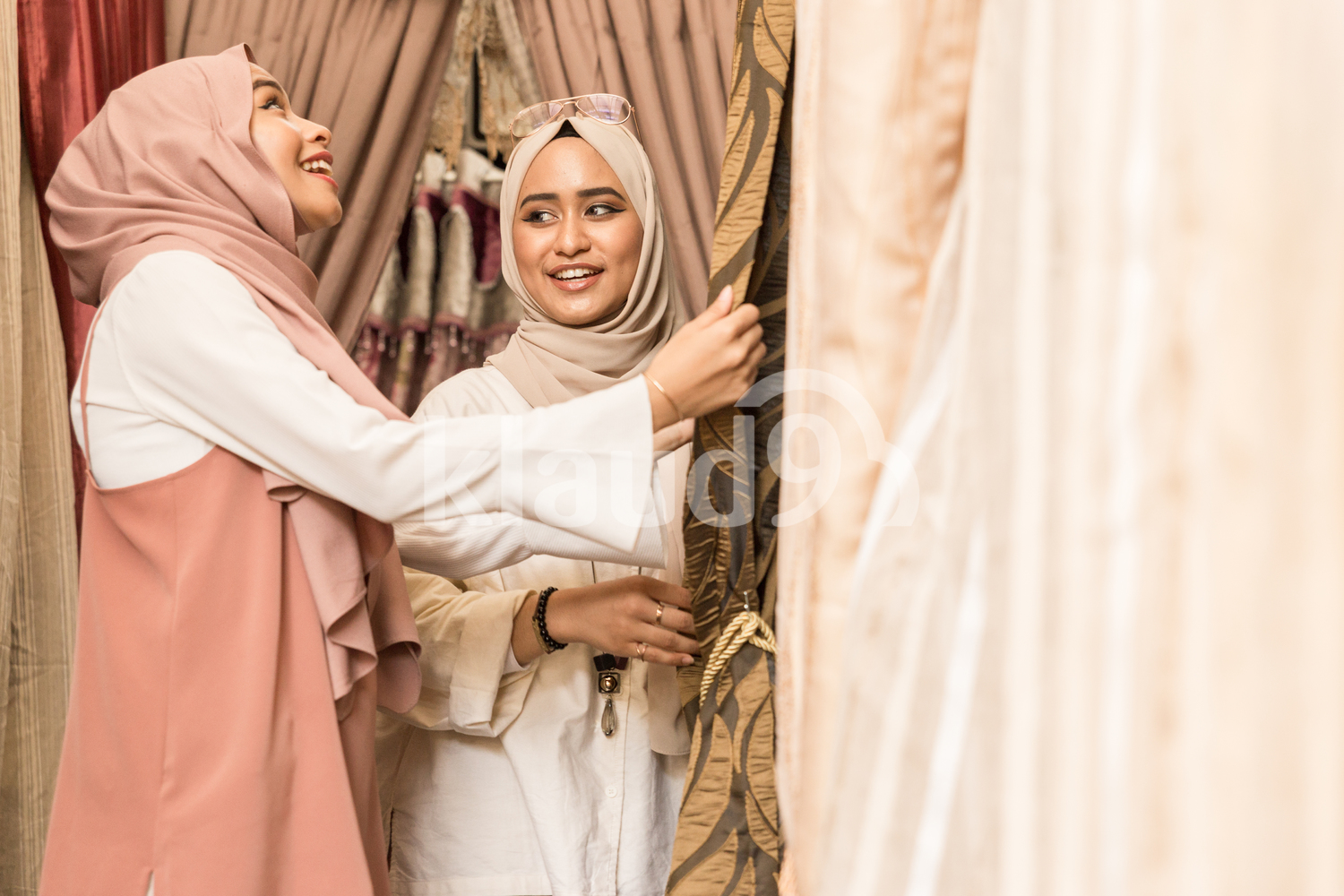 Two women in headscarves shopping for curtains
