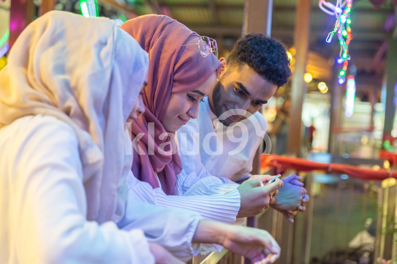 Three muslim friends looking down at mobile phone