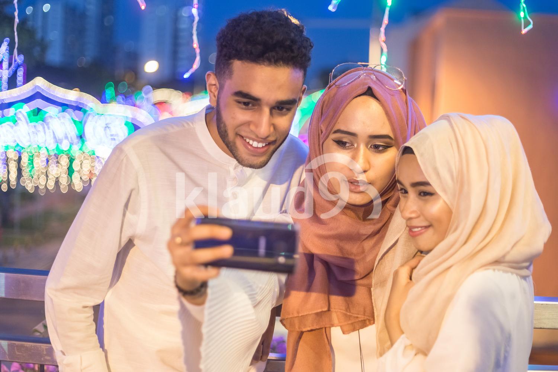 Three people taking selfies
