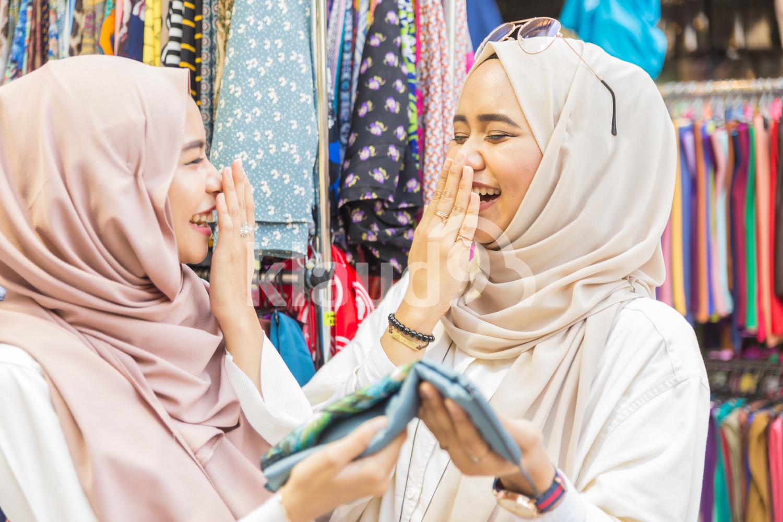 Young Muslim women shopping for fabrics