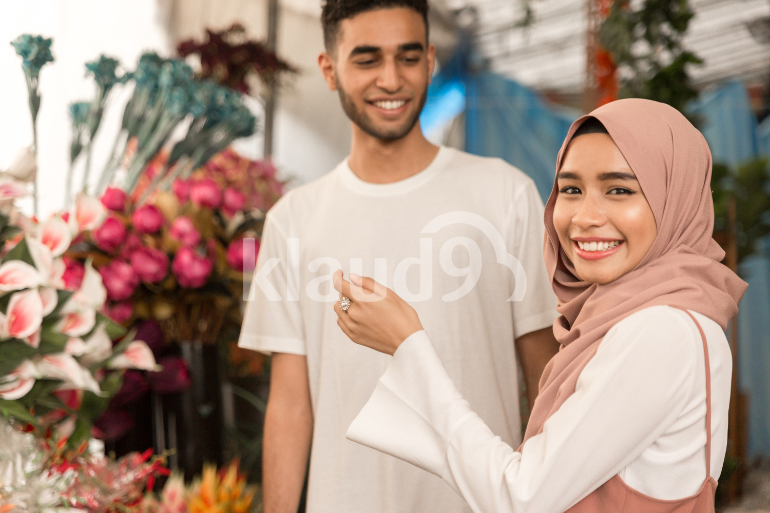Muslim couple in flower store smiling