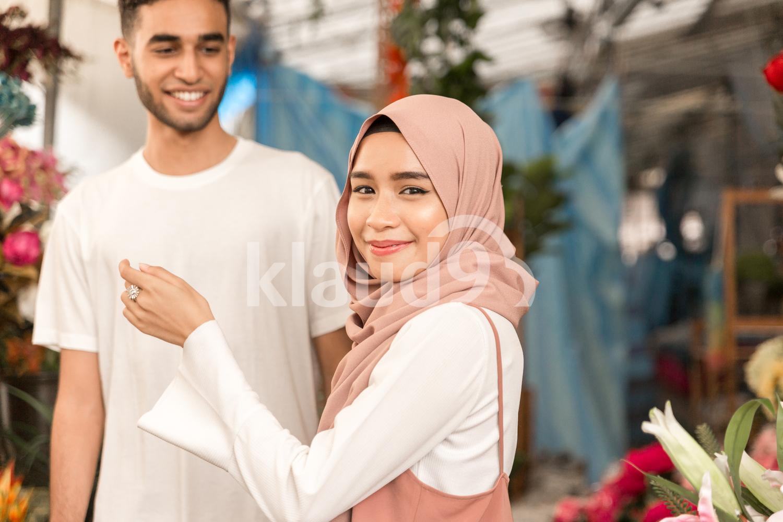 Muslim girl in flower shop looking in camera