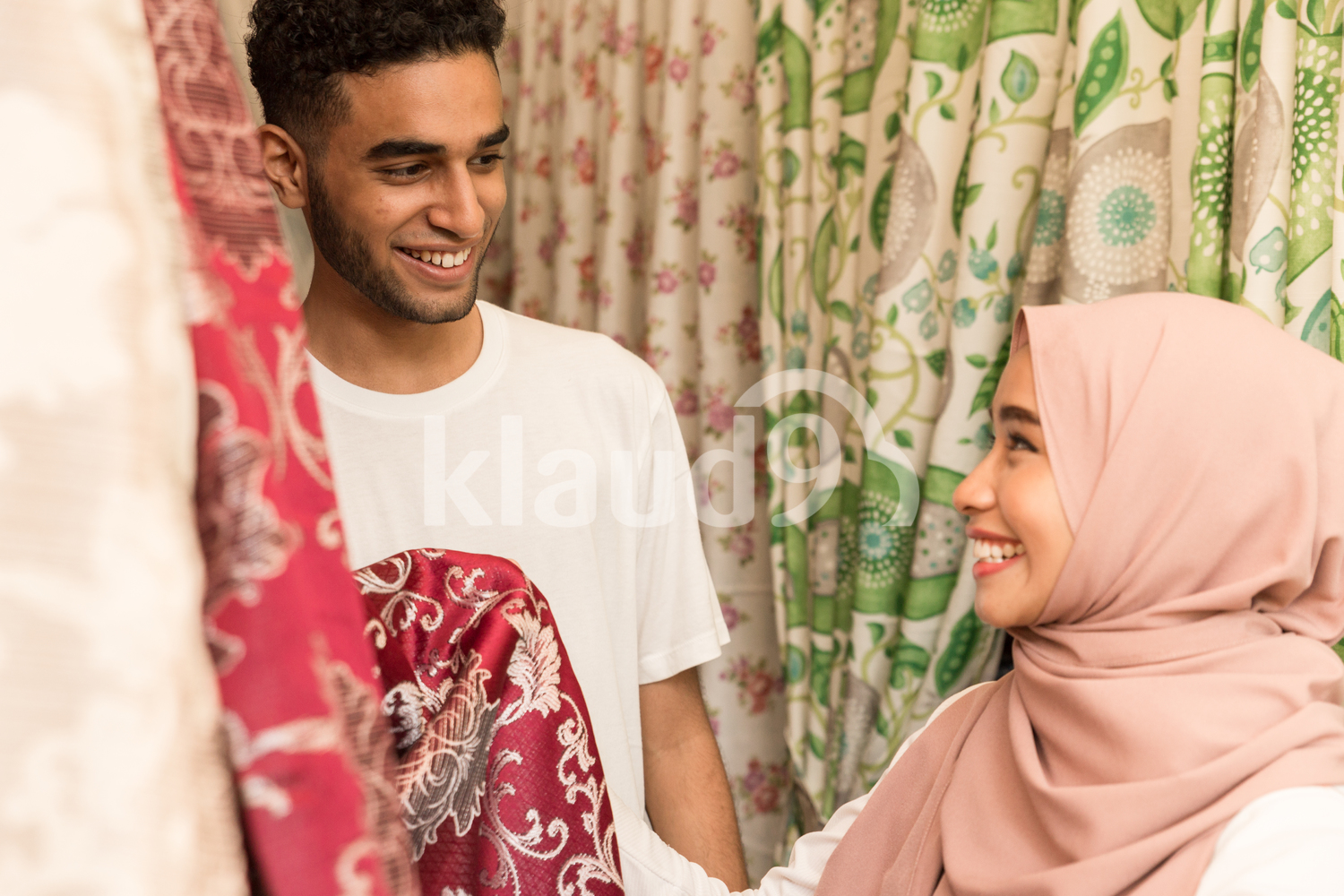 Young muslim couple smiling in fabric store