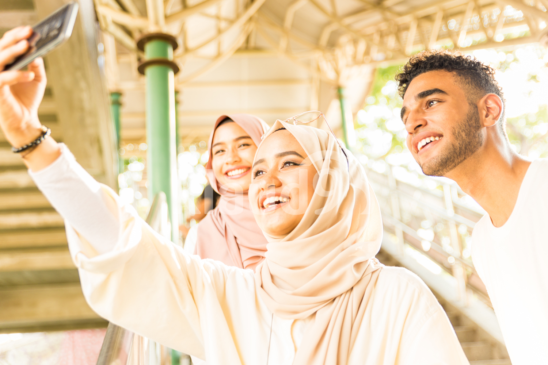 Three Muslim friends taking selfies