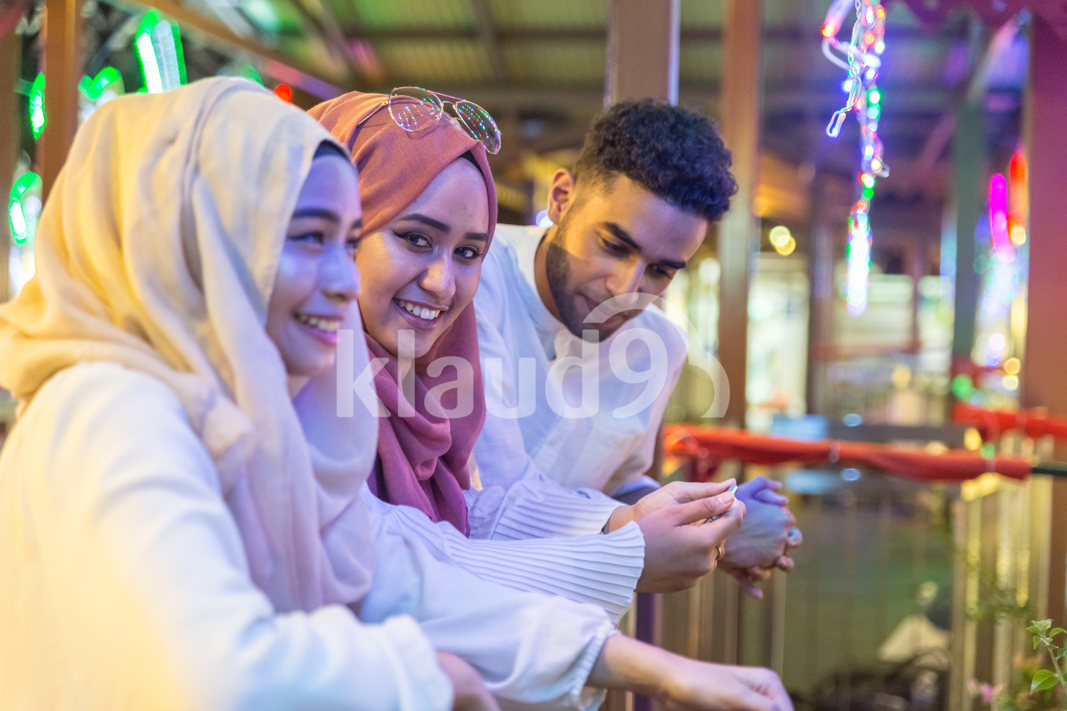 Young group of muslims are looking at a mobile phone