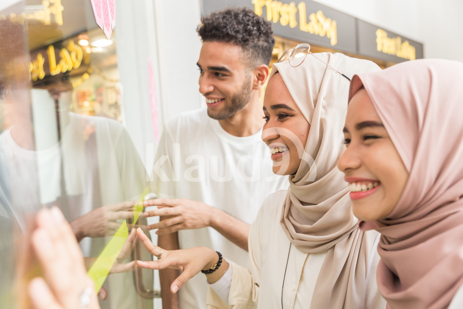 Young muslims looking into window