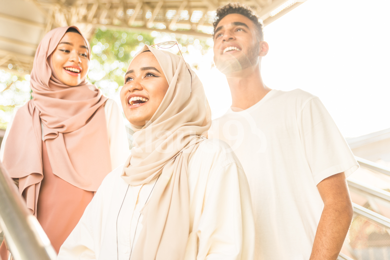 Three muslim friends on stairs smiling
