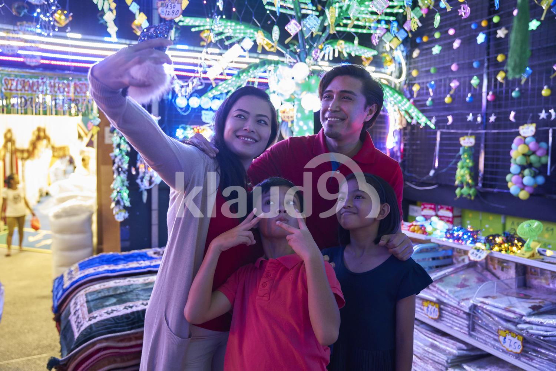 Young family taking selfies at Hari Raya Geylang Bazaar, Singapore