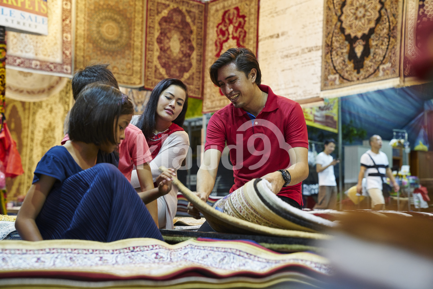 Young family browsing for carpets at Geylang Bazaar, Singapore