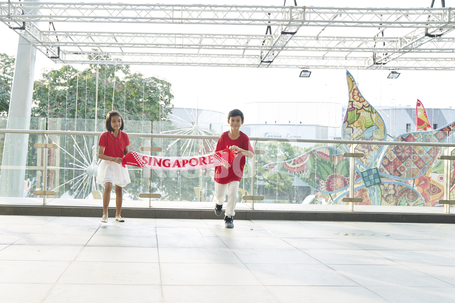 Two siblings celebrating Singapore's National Day
