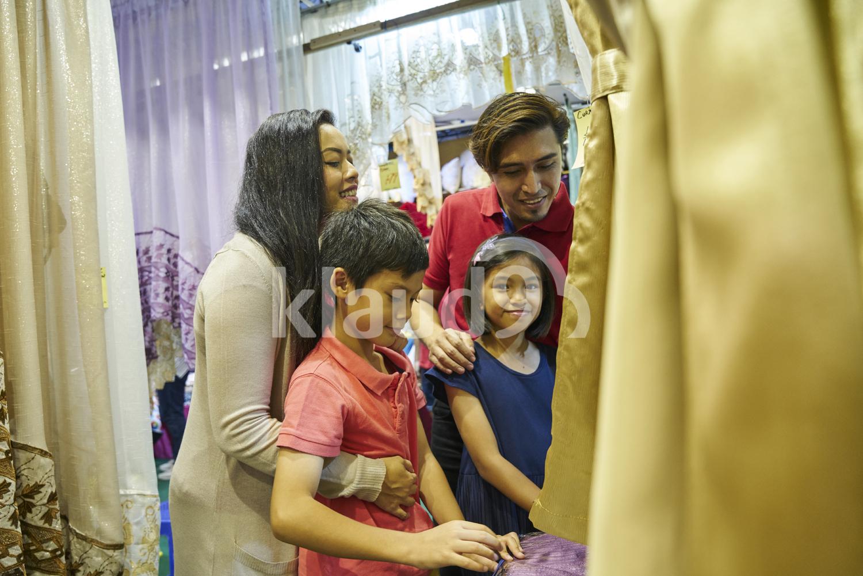 Family shopping for curtains during Hari Raya Bazaar at Geylang, Singapore