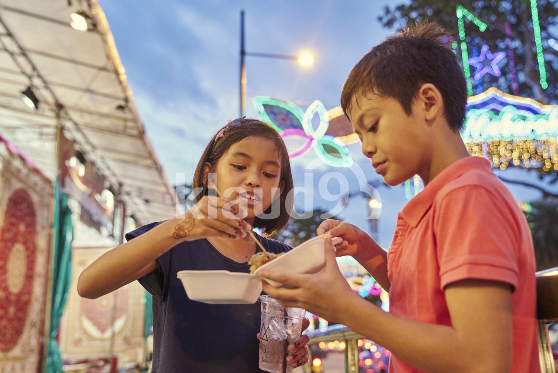 Siblings breaking fast at Hari Raya bazaar, Singapore