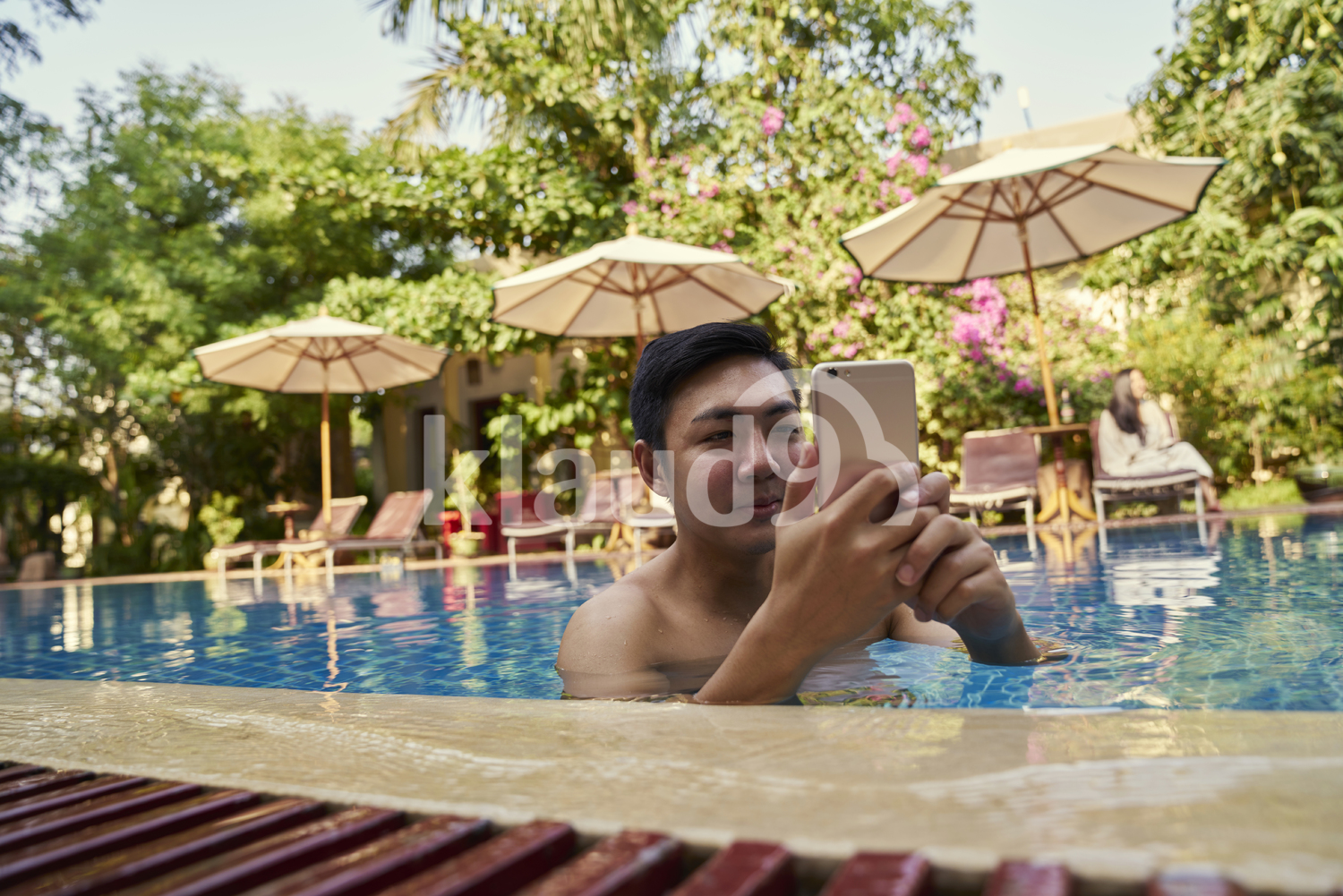 Young man taking photos with his mobile phone in the pool