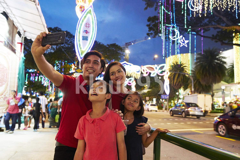 Happy family taking selfies at Hari Raya Geylang Bazaar, Singapore