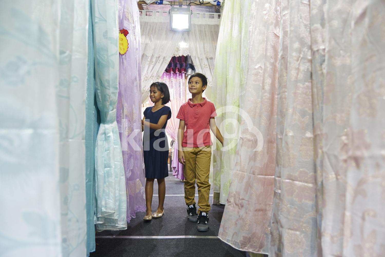 Siblings shopping for curtains during Hari Raya Bazaar at Geylang, Singapore