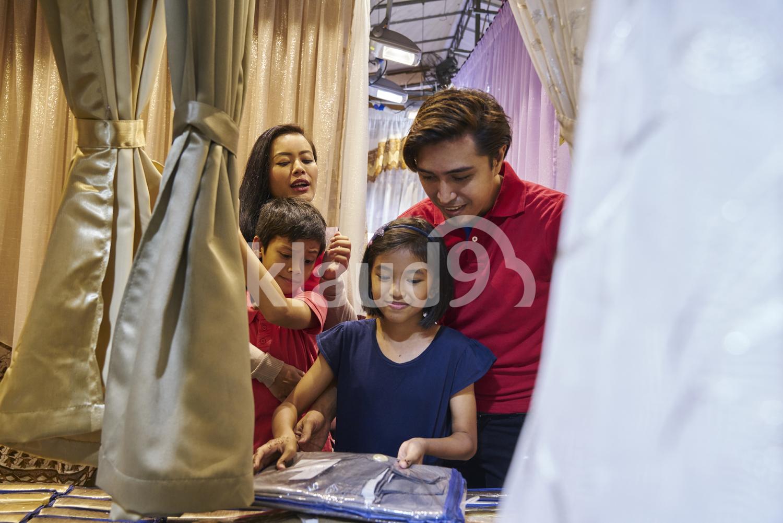 Happy family shopping for curtains during Hari Raya Bazaar at Geylang, Singapore
