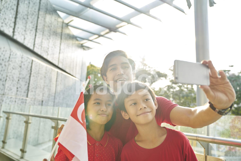 Cheerful family celebrating Singapore's National Day