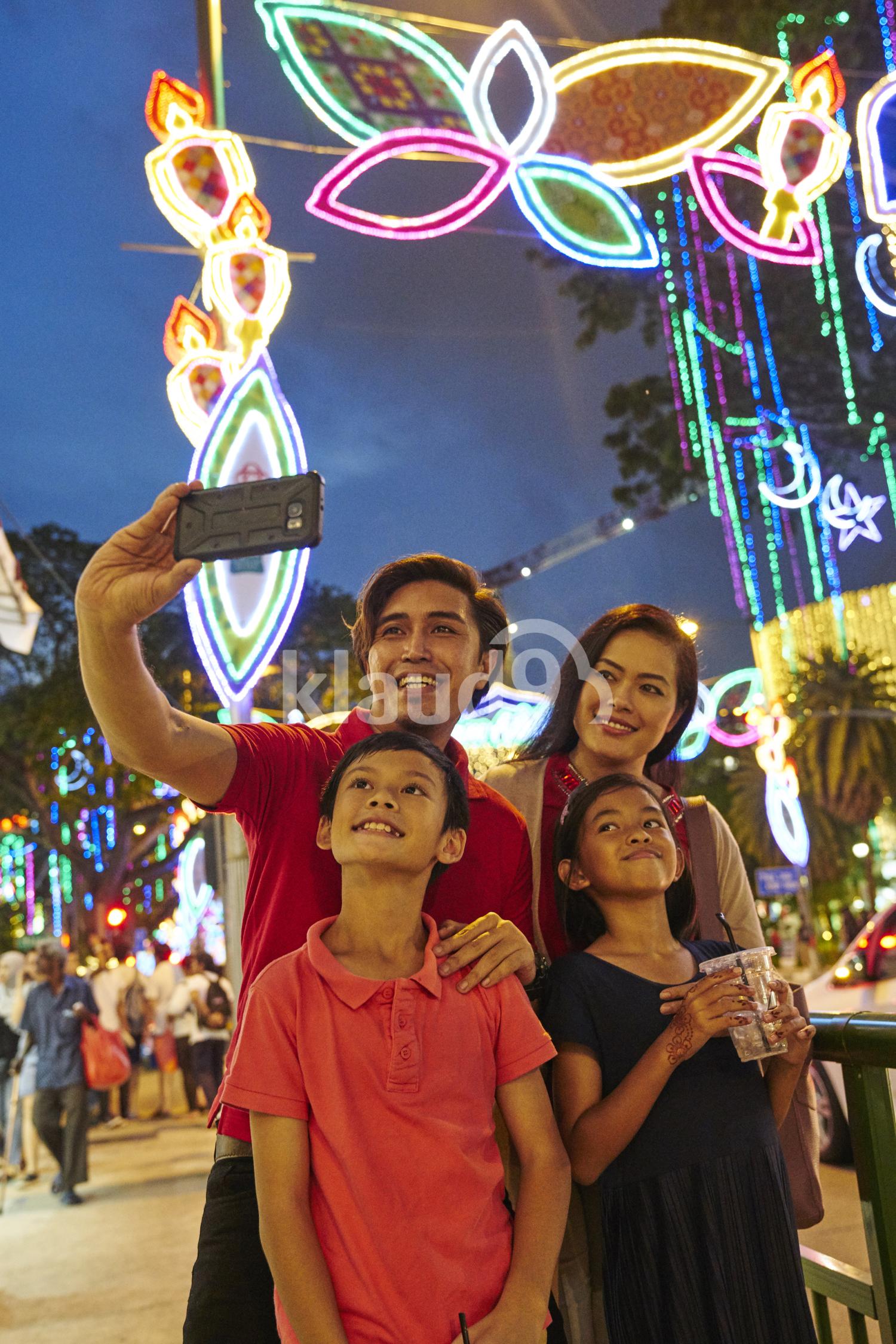 Smiling family taking selfies at Hari Raya Geylang Bazaar, Singapore