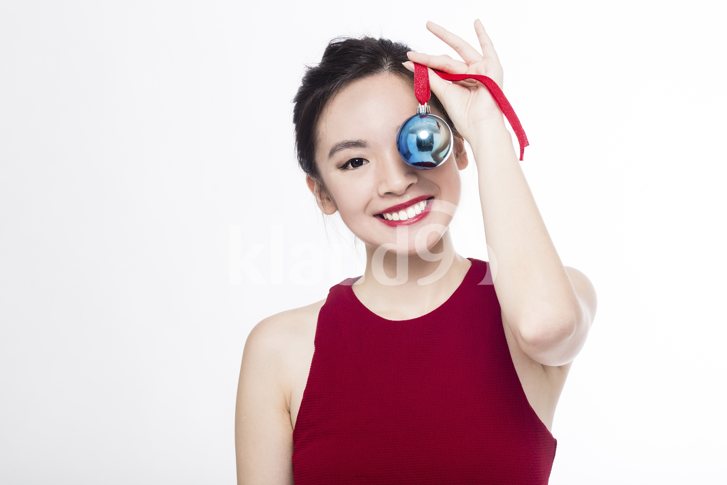 Happy Pan Asian woman with her Christmas ball ornament