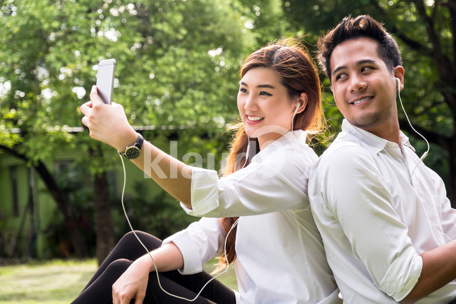Happy asian couple taking a selfie with smart phone camera in the park, lover and lifestyle concept