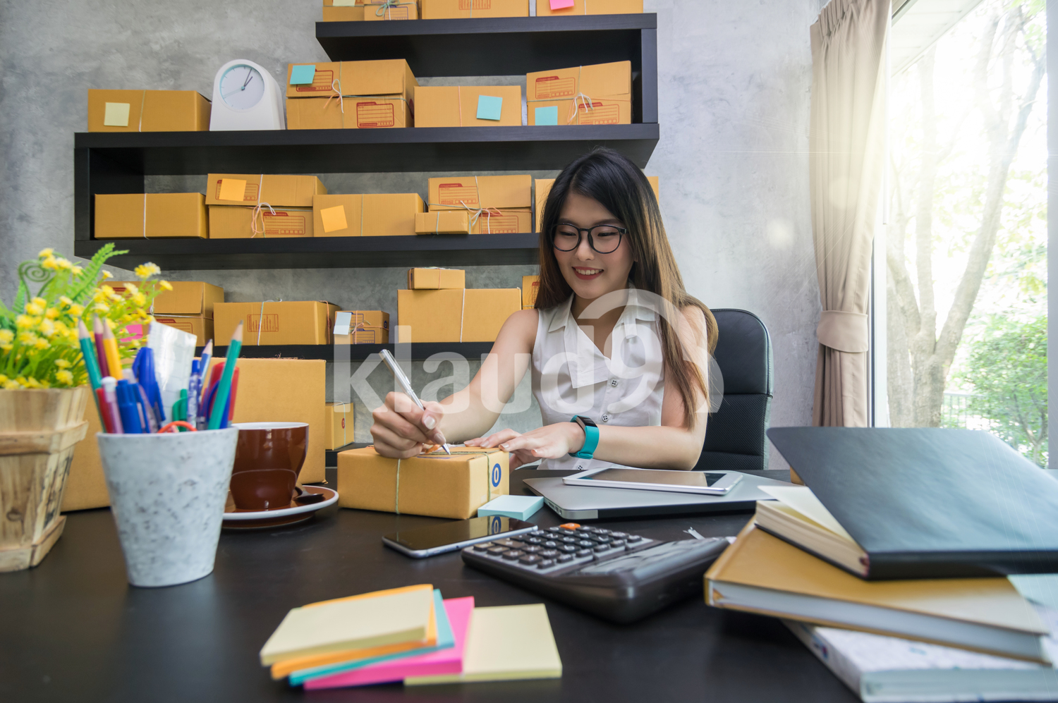Young business woman working from home preparing package for posting
