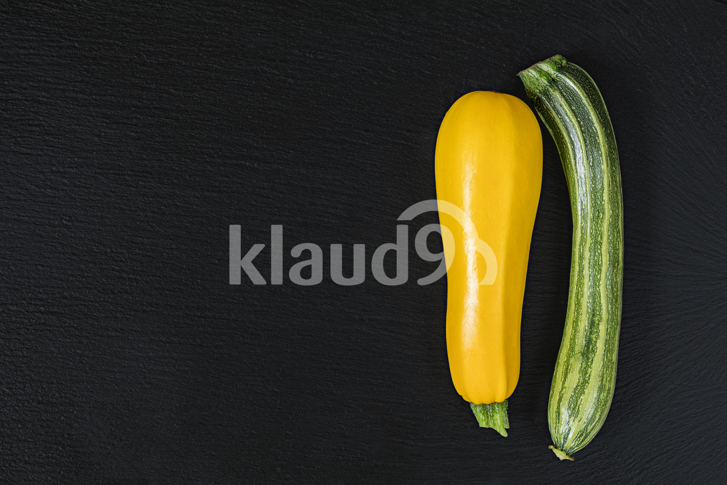 Striped fresh green zucchini and yellow zucchini on a black stone surface