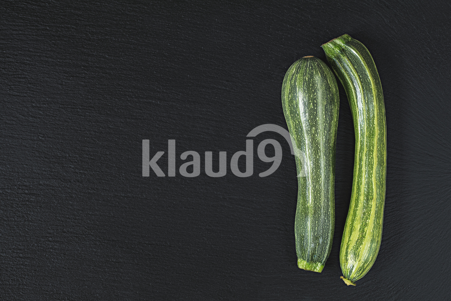 Two striped fresh green zucchini on a black stone surface