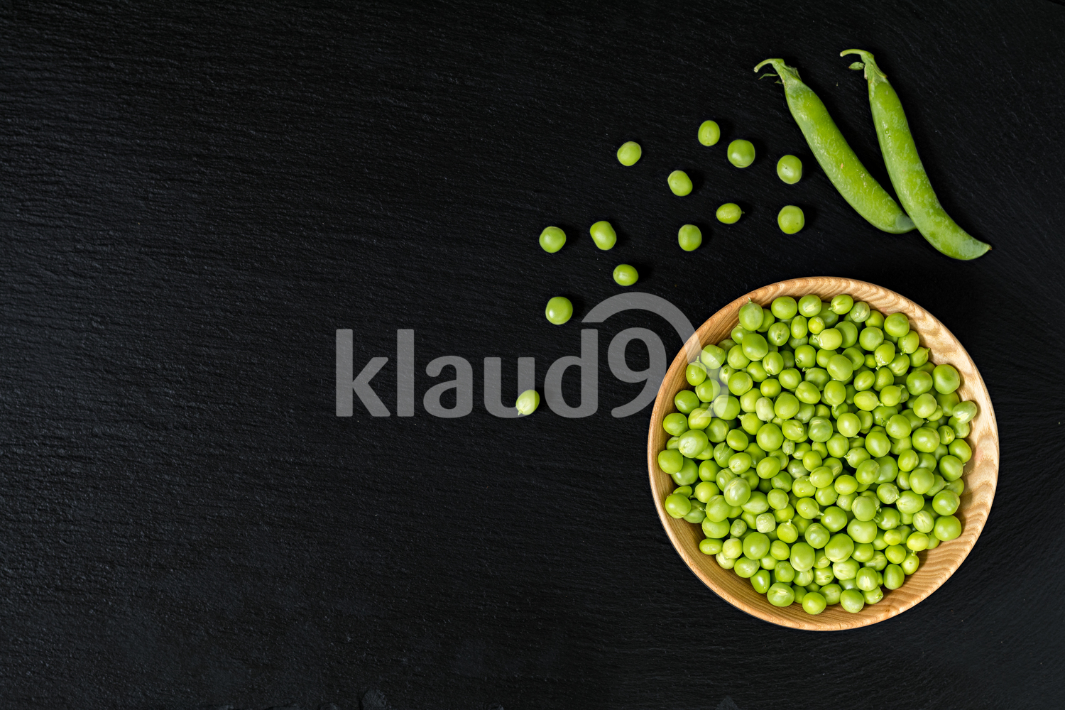 Grains fresh green peas in wooden bowl on a black stone surface.  Top view, copy space. Healthy eating concept.