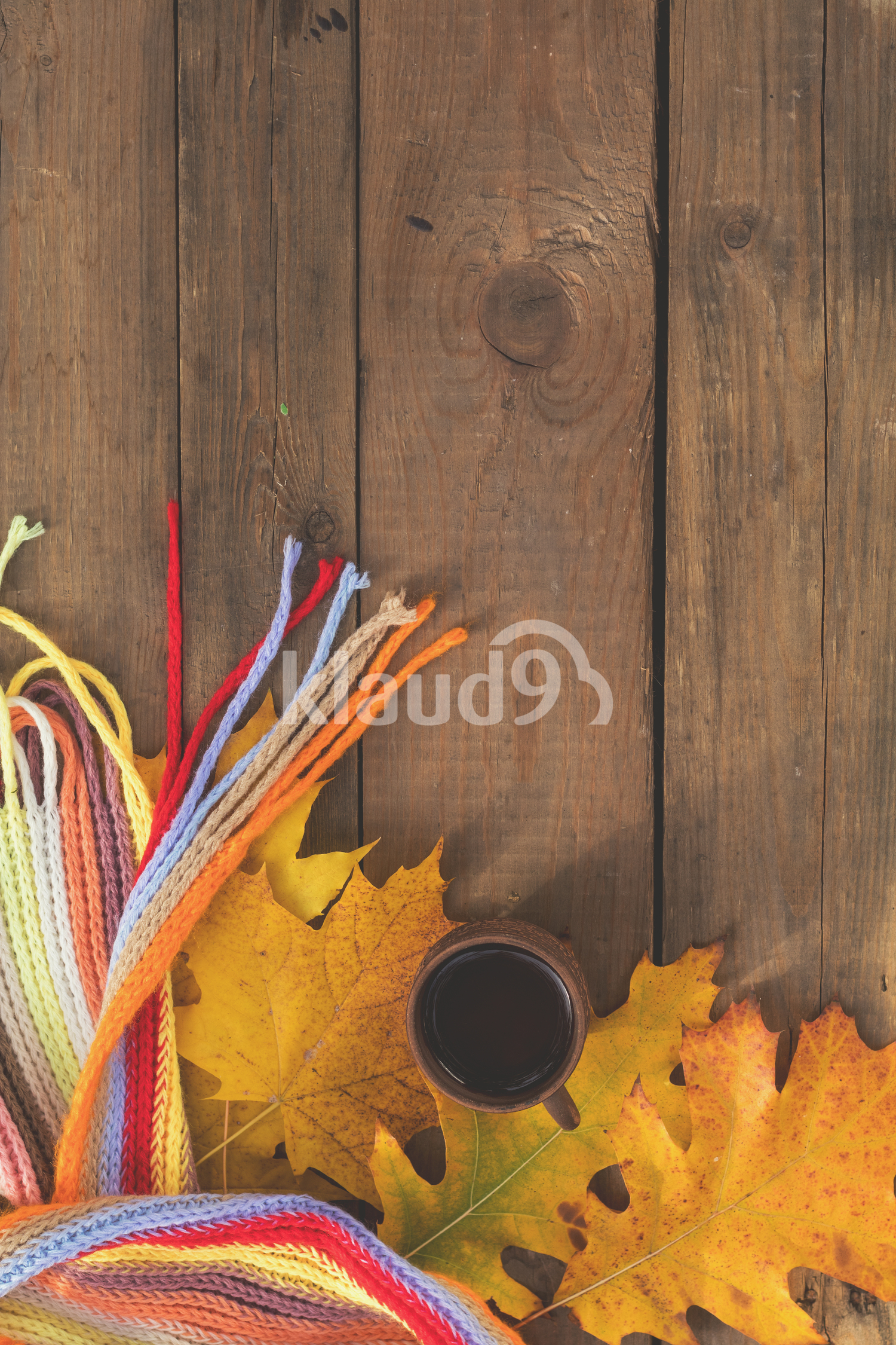Multicolored scarf, cup of coffee, yellow maple and oak leaves on the wooden board