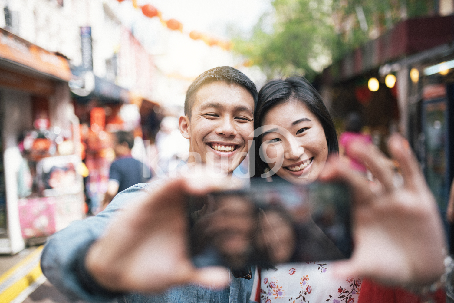 Chinese couple taking selfie on their mobile phone