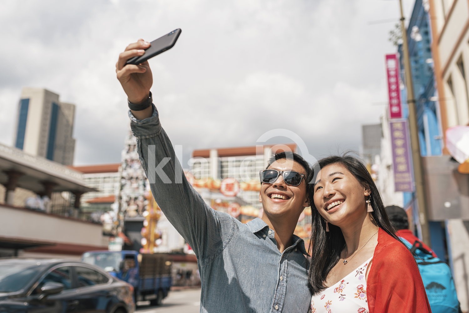Asian couple taking selfie on the streets