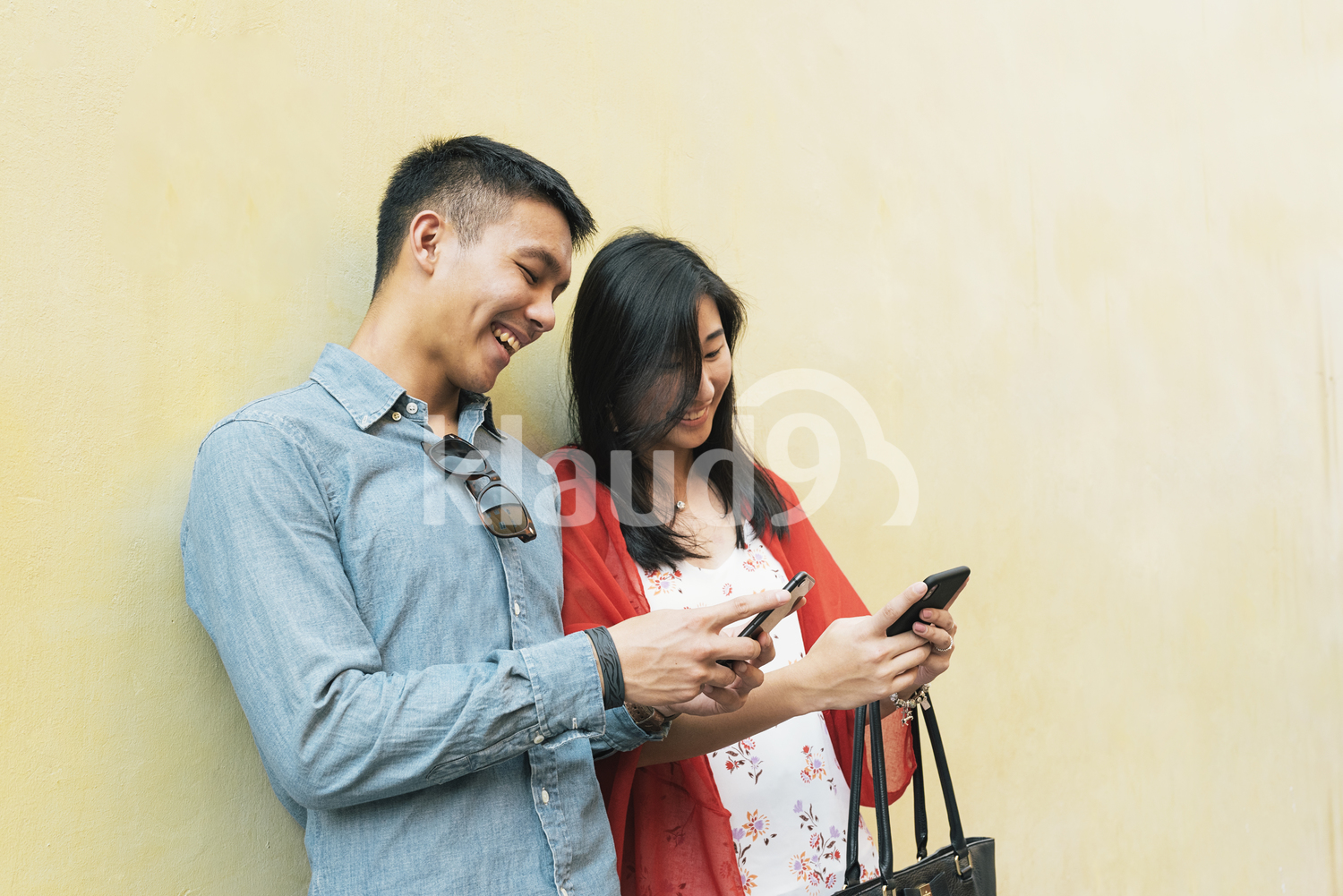Chinese couple reading text messages on their smartphone